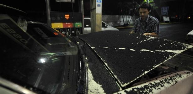 Homem limpa a cinza vulcânica que atingiu os carros no município de Villa Nueva, na Guatemala. A erupção do poderoso vulcão Pacaya obrigou a evacuação de diversas áreas