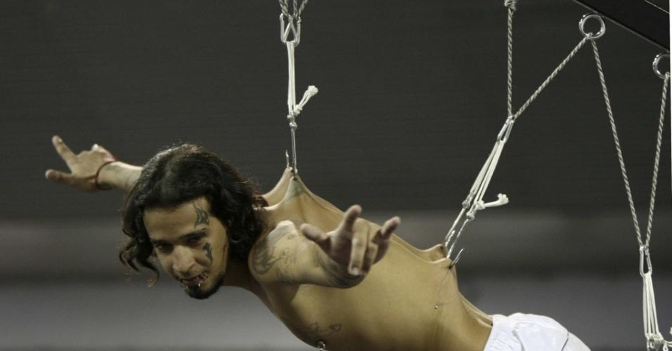Homem é suspenso por ganchos perfurados em sua pele, na Convenção Internacional de Tatuagem, em Bogotá, Colômbia