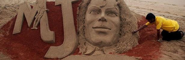 Homem retoca escultura de areia que homenageia Michael Jackson