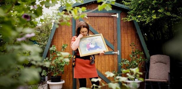Laurie Krausse com uma fotografia de seu falecido marido Bernd, que morreu de gliobastoma, no celeiro construído pelo casal no quintal de sua casa
