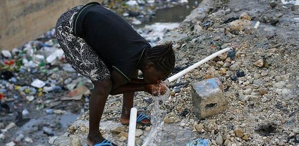 Menina bebe água em cano no Haiti