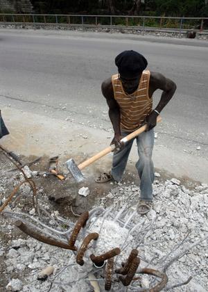 Estinel Eliusma tira, a marretadas, vergalhões de aço de um pedaço de muro jogado em terreno baldio de Porto Príncipe. Sem emprego, a saída é vender o metal retirado dos escombro