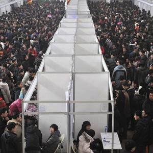 Milhares de chineses desempregados visitam uma feira de emprego na cidade de Shenyang, nordeste da China. Concorrência para os trabalhadores qualificados nos Estados Unidos