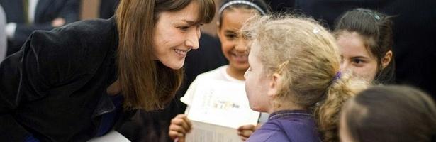 A primeira-dama da França, Carla Bruni-Sarkozy, conversa com crianças na Feira de Livros de Paris