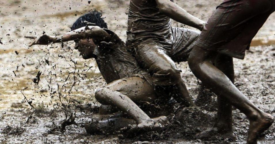 Jovens indianos jogam futebol na chuva em terreno cheio de lama em Mumbai, na Índia
