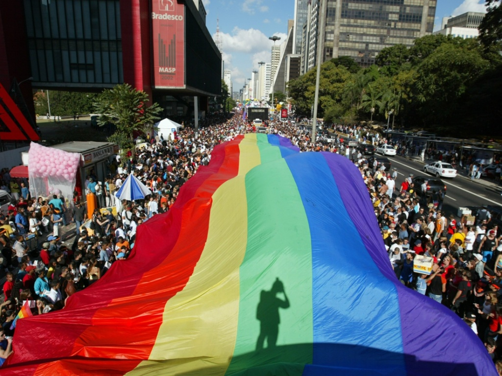Participantes da Parada do Orgulho Gay de So Paulo com bandeira na avenida Paulista