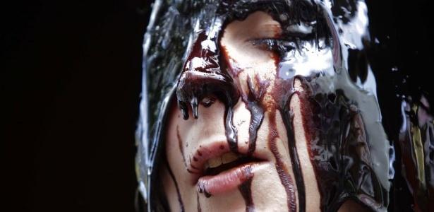 Mulher joga geleia no rosto para protestar contra a exploração de óleo derivado de petróleo no Canadá, em manifestação realizada em Viena, na Áustria