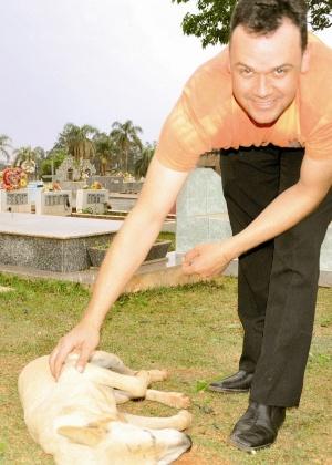 Vira-latas Rambo é acariciado pelo coveiro Sidinei Ramos em cemitério de Mamborê (PR), para onde o cachorro se mudou após morte do dono, há 4 meses