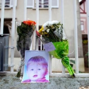 Uma foto de Bastien e flores são deixados na entrada da casa dos pais da criança, na França