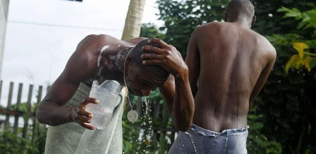 Haitianos tomam banho em um chuveiro improvisado em Iñapari, fronteira do Peru com o Brasil