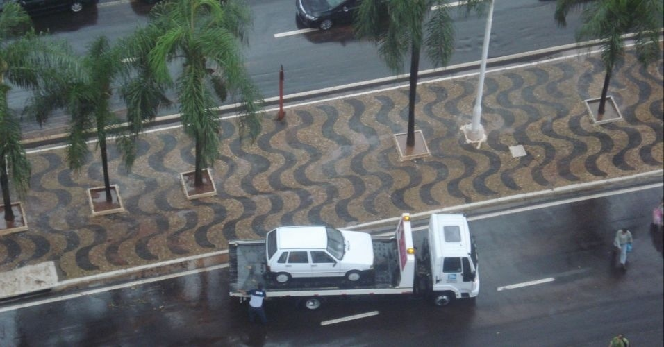 10.mar.2012 - Carro que ficou preso em alagamento (dir.) é rebocado em avenida de São José do Rio Preto (SP), após temporal que atingiu a cidade