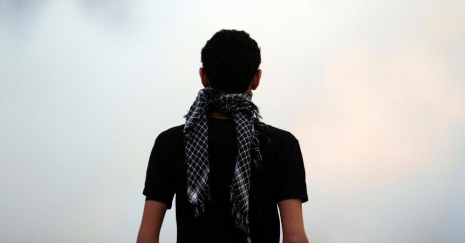 Bareinita caminha entre fumaça de bombas de gás lacrimogêneo lançadas pela polícia em Diraz, no Bahrein