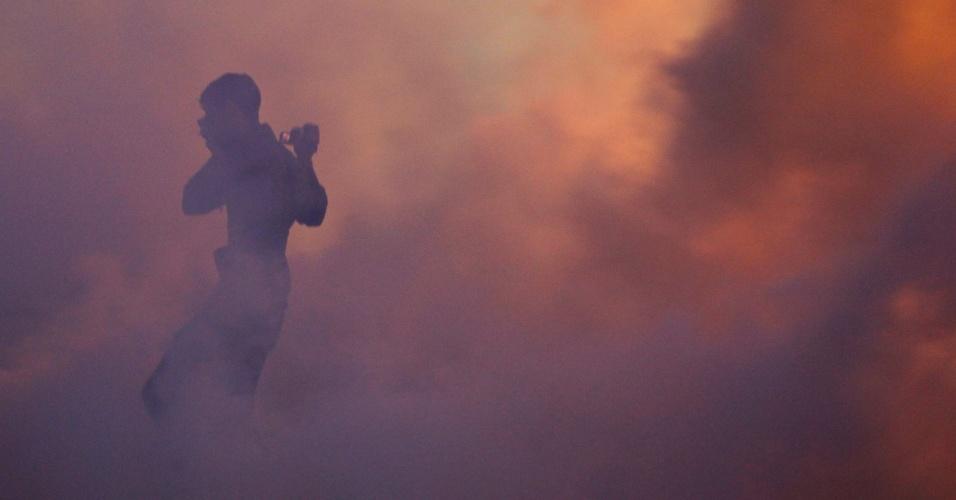 Bareinita foge de fumaça de gás lacrimogêneo lançado pela polícia em Diraz