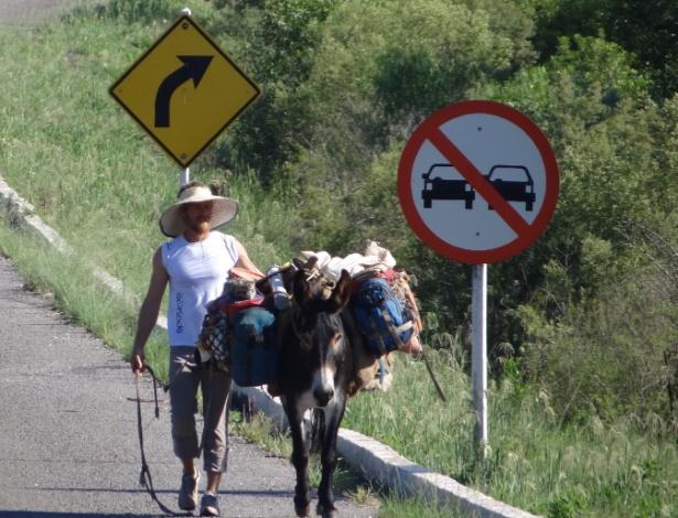 O americano Jonathan Dunham e seu companheiro, o burro Judas, caminham em beira de estrada gaúcha