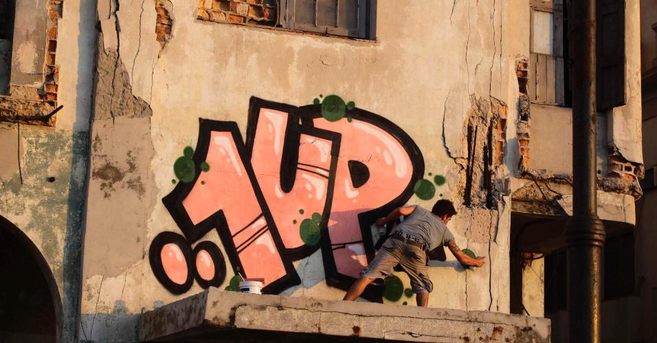 Grafiteiro pinta parede de prédio no El Malecon, em Havana, em Cuba