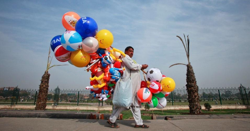 Homem carrega bolas de praia e brinquedos infláveis próximo a parque em Lahore, no Paquistão