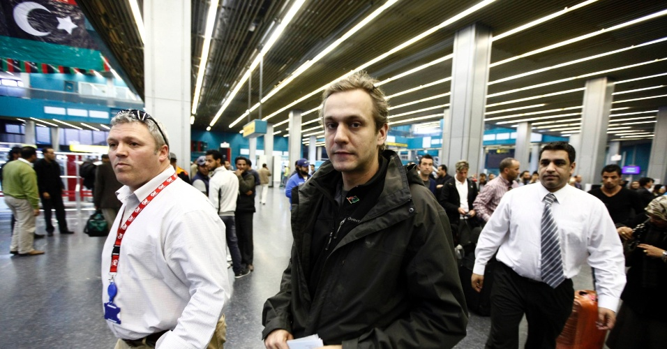 """Jornalista britânico Nicholas Davies-Jones (centro) caminha nesta segunda-feira (19) no Aeroporto Internacional de Trípoli, na Líbia, antes de embarcar para o Reino Unido. Davies e o cinegrafista Gareth Montgomery-Johnson, que trabalham para o canal de televisão iraniana """"Press TV"""", foram presos em Trípoli no dia 22 de fevereiro por uma milícia da cidade líbia de Misrata"""