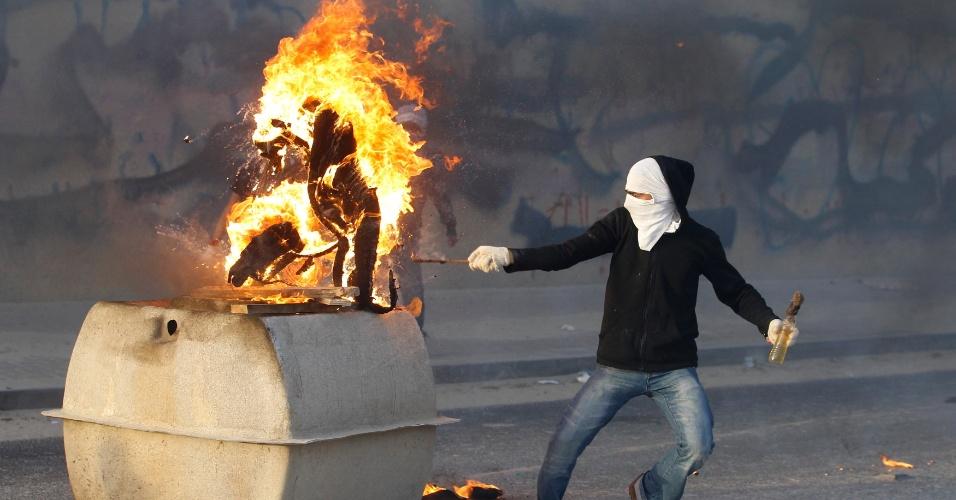 Manifestante coloca fogo em um tanque de água durante protesto realizado no sul da aldeia de Manama, capital do Bahrein, após o funeral de Sabri Mafooz, que morreu por inalar gás lacrimogêneo disparado por policiais