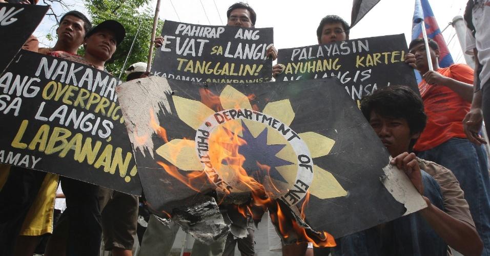 Manifestantes filipinos queimam o logotipo do Ministério de Energia das Filipinas em protesto contra o aumento dos preços da gasolina na cidade de Taguig