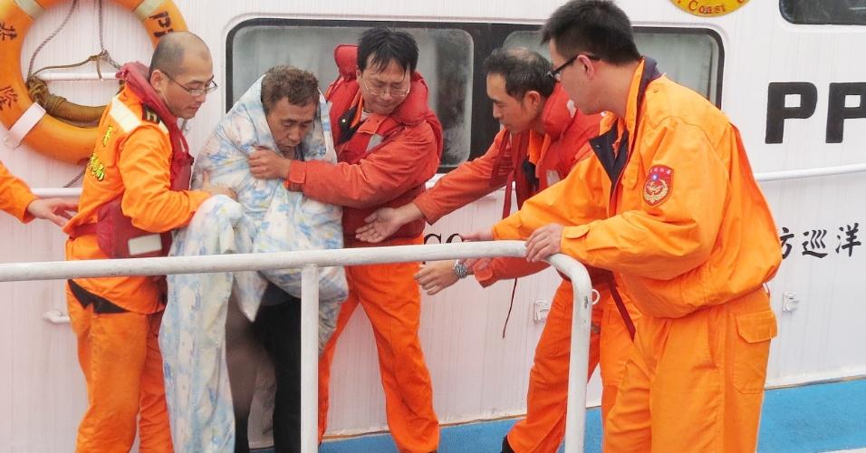 Marinheiro é ajudado por Membros da Guarda Costeira taiwanesa em barco de patrulha no porto de Keelung, em Taiwan