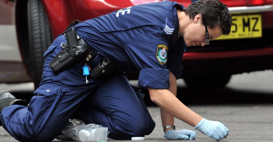 Perito examina local onde um homem, possivelmente brasileiro, morreu ao ser atingido por uma pistola paralisante em Sydney, Austrália