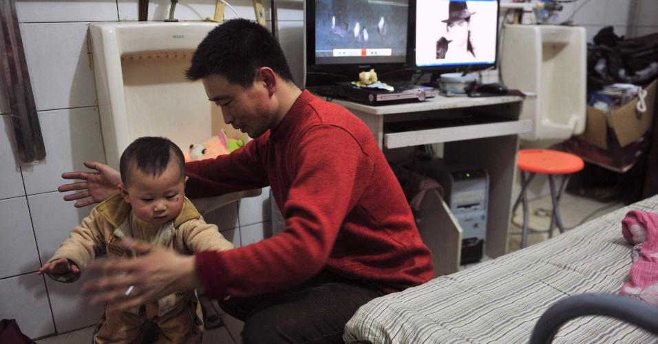 Zeng Lingjun brinca com seu filho ao lado de mictório em hotel de Shenyang, na China