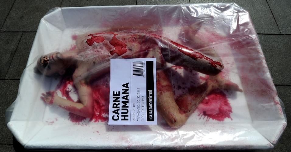 Ativistas dos direitos dos animais se embalam em bandejas gigantes e pedem o dia mundial sem carne na praça da catedral de Barcelona, na Espanha
