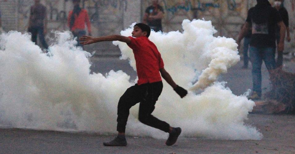 Bareinita recolhe do chão bomba de gás lacrimogêneo lançada pela polícia em Manama, capital do Bahrein