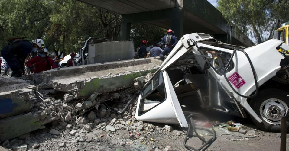 Bombeiros trabalham para remover um ônibus que foi atingido por uma ponte que desmoronou na Cidade do México após um forte terremoto que atingiu o sul do México