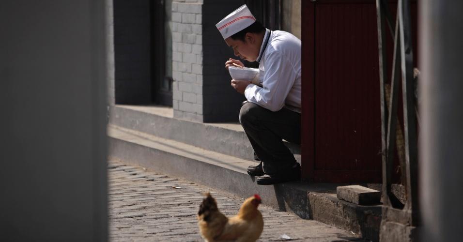 Cozinheiro faz refeição na entrada dos fundos de restaurante no centro de Pequim, na China