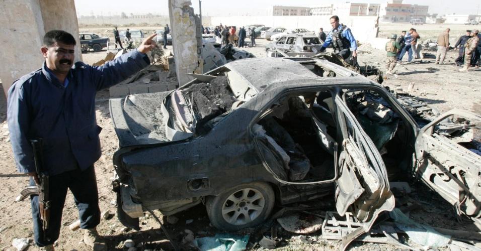 Forças de segurança iraquianas inspecionam destroços de um carro-bomba na cidade de Kirkuk