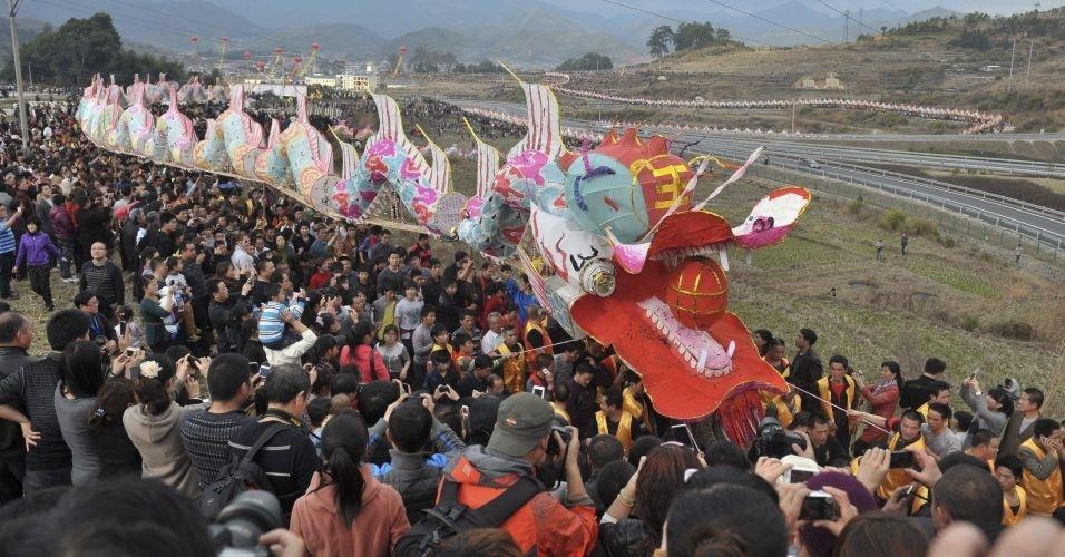"""Grupo de pessoas ajuda a transportar """"carroça de dragão"""" com 791,95 metros de comprimento no templo de Gutian, em Liancheng, província de Fujian, na China. A geringonça foi registrada pelo Livro dos Recordes como a maior carroça de desfiles do mundo"""