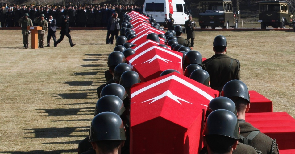 Guarda de honra turca carrega caixões com o corpo de soldados mortos em uma queda de helicóptero no Afeganistão, durante cerimônia na base militar de Ancara, na Turquia. Um helicóptero da Otan caiu em uma casa na periferia de Cabul, no Afeganistão e matou 12 soldados turcos a bordo, na sexta (16)