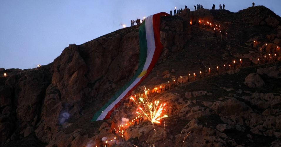 Iraquianos percorrerem a cidade de Akra, no Iraque, segurando tochas como a bandeira curda para celebrar o novo ano que marca o início do festival de primavera Nowruz