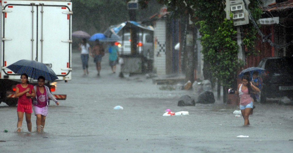 Moradores caminham por rua alagada durante forte chuva que atingiu Belém, no Pará