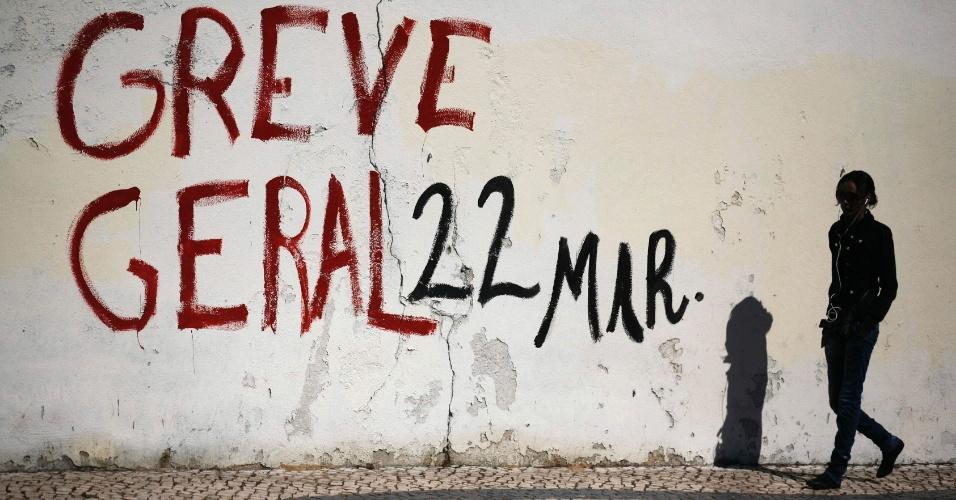 """Mulher passa por parede grafitada com mensagem chamando para uma """"greve geral"""" na próxima quinta-feira, 22 de março, em Lisboa, Portugal. A greve é contra as reformas de mercado provocadas pela crise econômica no país"""