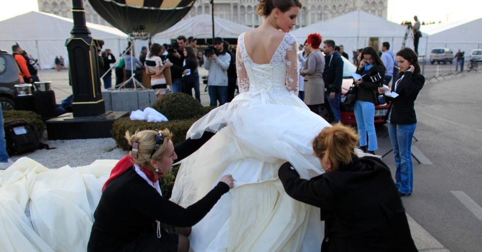 Mulheres ajudam na preparação da cauda de vestido de noiva mais longa do mundo incluída no Guiness em Bucareste, na Romênia