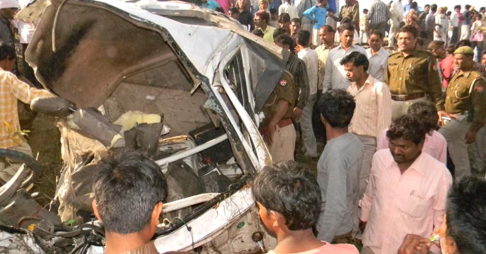 Policiais e curiosos observam os destroços após colisão entre trem e caminhonete que levava 25 pessoas no distrito de Mahamaya Nagar, na Índia