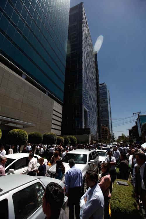 Trabalhadores são vistos do lado de fora de um edifício após um forte terremoto que atingiu a Cidade do México