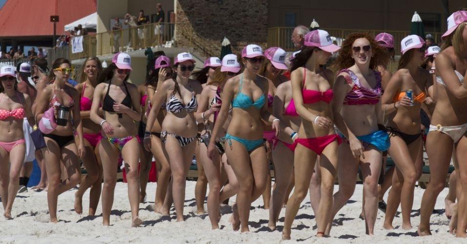 """Um grupo de 450 mulheres usando biquíni bateu o recorde de """"maior marcha de biquini do mundo"""", em praia da Flórida, Estados Unidos. O recorde superou a marca registrada na Austrália, que contou com 357 mulheres, em outubro passado"""