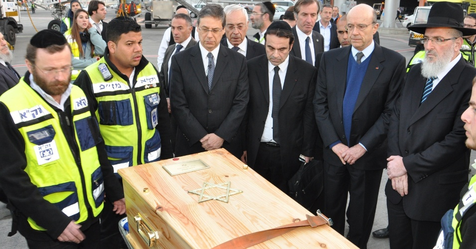 21.mar.2012 - Voluntários rezam nos caixões de Rabbi Jonathan Sandler, 30, de seus filhos Arieh, 5, e Gabriel, 4, e da garota Miriam Monsonego, 7, para o funeral. Eles morreram durante tiroteio em escola judia de Toulouse, na França