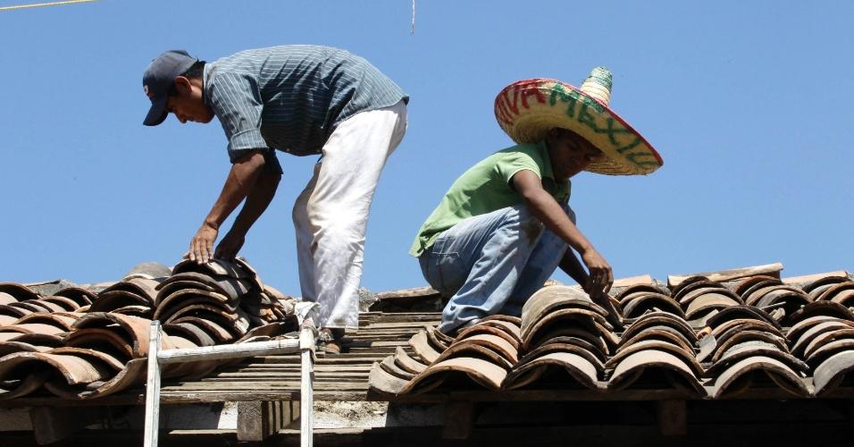 Mexicanos arrumam telhado danificado por terremoto que atingiu a cidade de Ometepec, no México