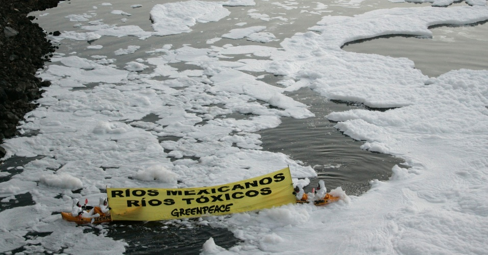 Ativistas do Greenpeace sentados em caiaque seguram bandeira para protestar contra a poluição do rio Santiago, no estado mexicano de Jalisco