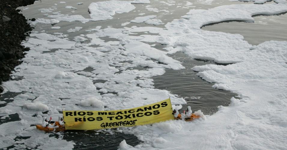 Ativistas do Greenpeace sentados em caiaque seguram bandeira para protestar contra a poluição do rio Santiago, no estado mexicano de Jalisco