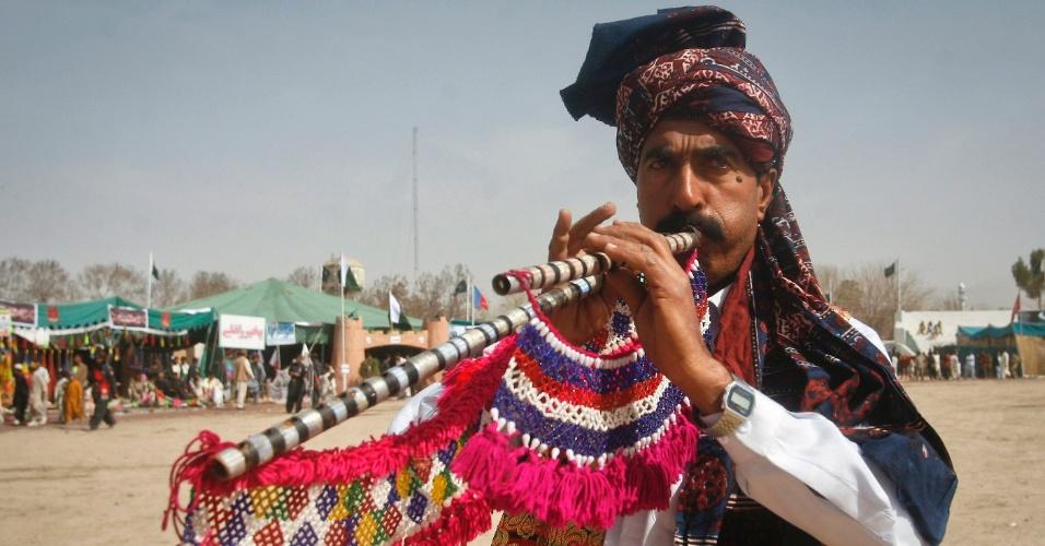 Homem toca flauta tradicional durante celebrações, em Quetta, pelo Dia do Paquistão