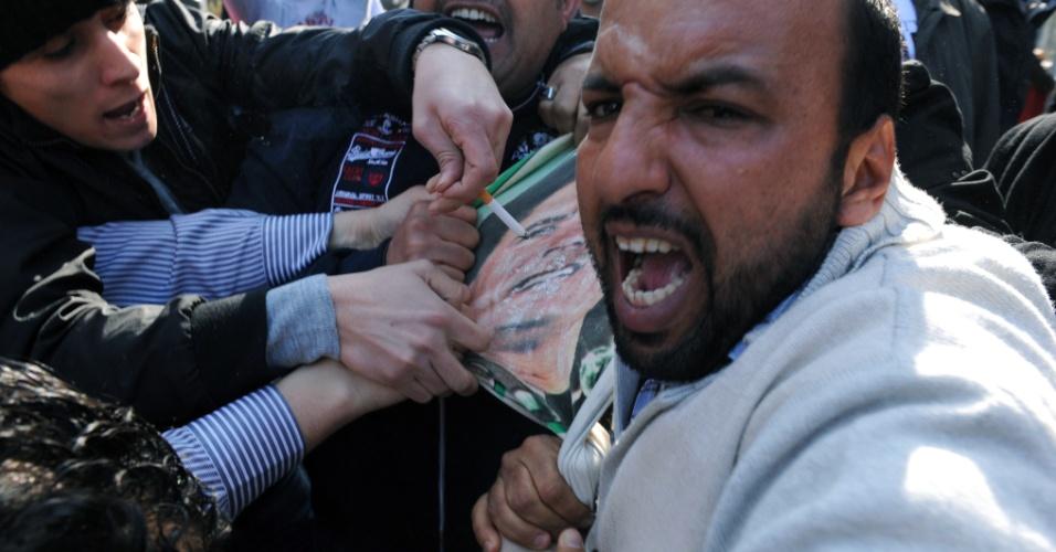 Líbios que exigiam ajuda financeira em frente ao consulado da Síria em Istambul, na Turquia, reagiram ao ver um cartaz com a imagem do ex-ditador líbio Muammar Gaddafi (centro)