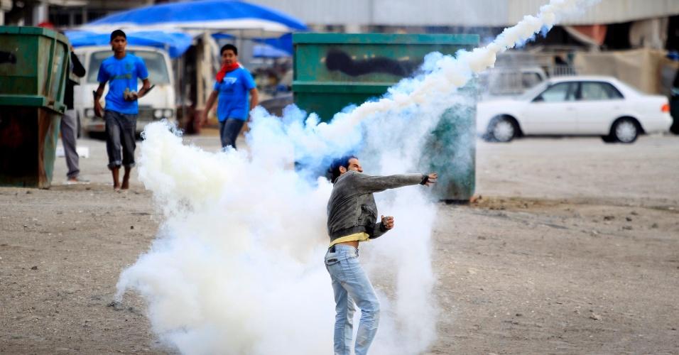 Manifestante atira de volta uma bomba de gás lacrimogêneo lançada pela polícia durante protestos na cidade de Jidhafs, a oeste de Manama. Nesta sexta-feira (23), milhares de pessoas tomaram as ruas de povoados xiitas próximos a capital, pedindo mudanças no regime político do Bahrein