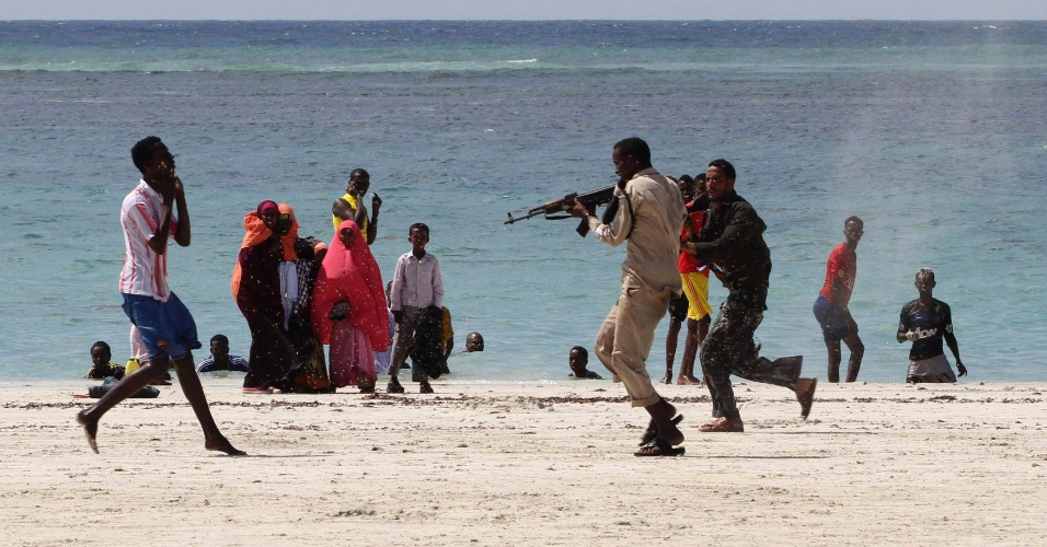 Policial somali aponta arma, em praia de Mogadício, capital da Somália, para suspeito (à esq.) de formar parte do grupo rebelde Al-Shabaab