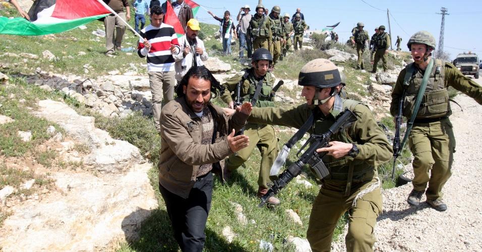 Soldados israelenses tentam impedir passagem de manifestante palestino em Maasarah, na Cisjordânia