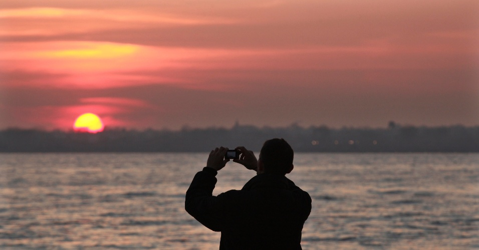 Turista fotografa pôr do sol no Parque Battery, em Nova York, nos Estados Unidos